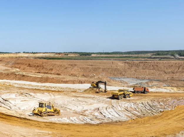 Excavator loading sand into dump trucks. sand mining in the quarry. Premium Photo