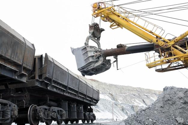 The excavator loads the stones into the cars. Premium Photo
