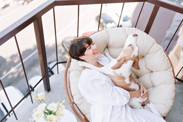 Ragazza eccellente con un sorriso affascinante gode di sabato mattina sul balcone che tiene divertente cane beagle Foto Gratuite