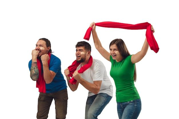 素晴らしい目標。白いスタジオの背景に分離された明るい感情を持つお気に入りのスポーツチームを応援する3人のサッカーファンの女性と男性。 無料写真