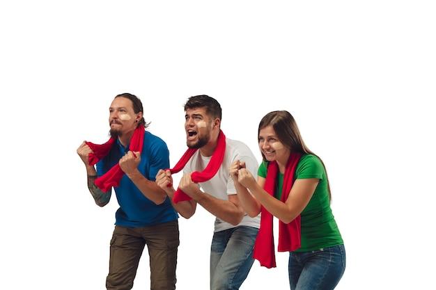Obiettivo eccellente. tre tifosi di calcio donna e uomini che tifano per la squadra sportiva preferita con emozioni luminose isolate su sfondo bianco studio. Foto Gratuite