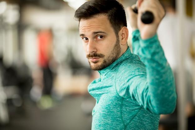 Человек делает excersise на машине lat в тренажерном зале Premium Фотографии