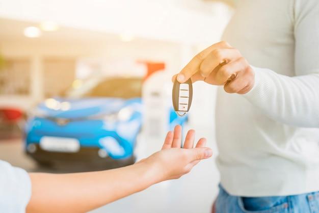 Exchanging keys in car dealership Free Photo