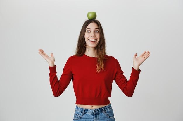 Возбужденная и веселая девушка улыбается, держа яблоко на голове Бесплатные Фотографии
