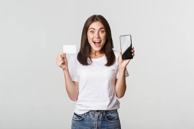 화면에 신용 카드 및 휴대 전화 뱅킹 앱을 보여주는 흥분하고 놀란 귀여운 소녀. 무료 사진