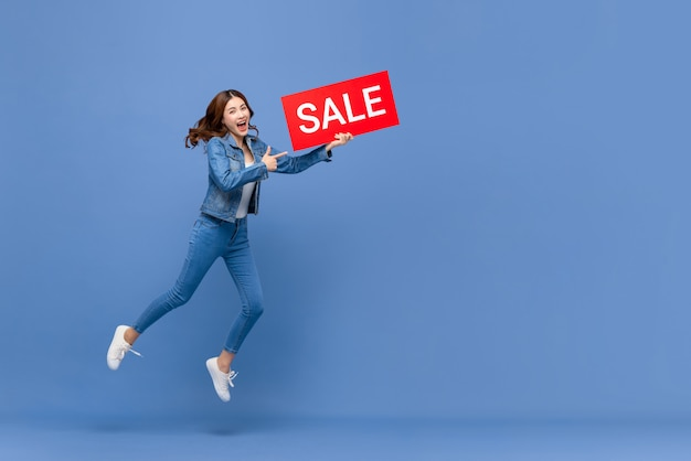 Excited asian woman jumping with red sale sign Premium Photo