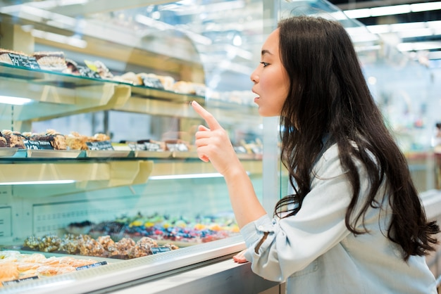 Excited asian woman pointing on dessert in pastry store Free Photo