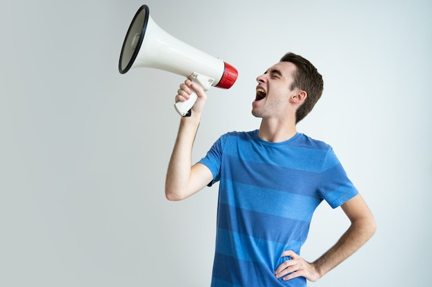 Excited attractive man shouting into megaphone Free Photo