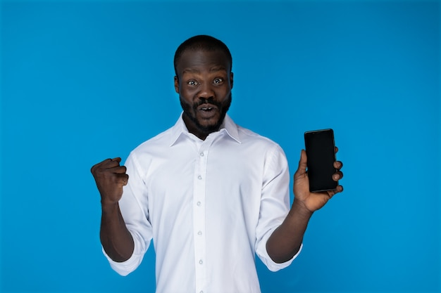 Excited bearded afro american guy is showing cell phone Free Photo