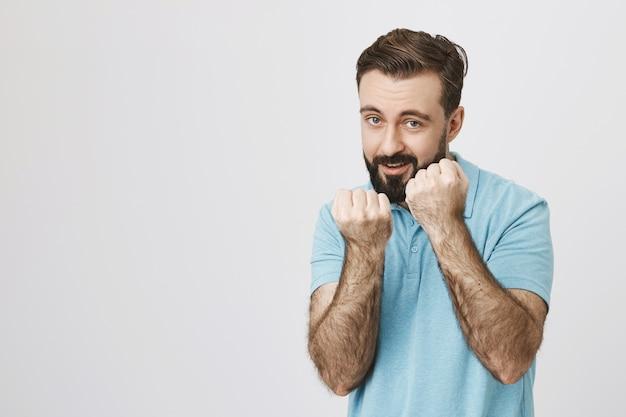 Il ragazzo barbuto eccitato vuole combattere, sorridendo Foto Gratuite