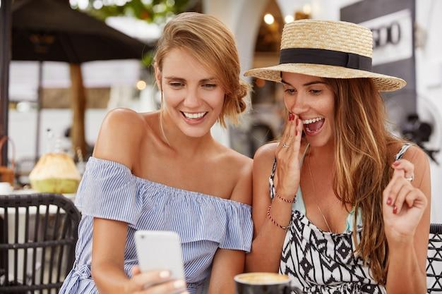 興奮した美しい2人の女性は、現代の携帯電話で面白いビデオを見て、驚いて幸せそうな表情をし、高速インターネットに接続された屋外の食堂で無料のタインを過ごします。 無料写真