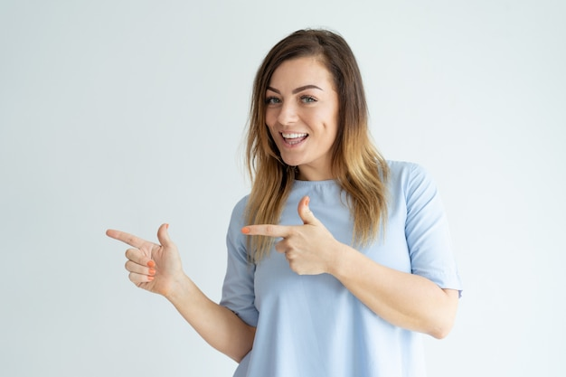 Excited beautiful woman pointing aside with both forefingers. Free Photo