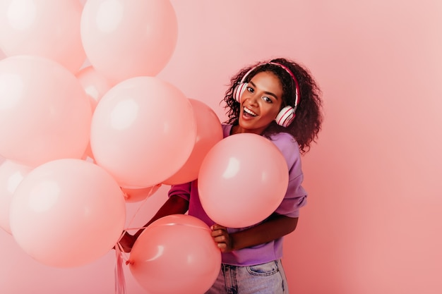풍선과 함께 포즈를 취하는 큰 헤드폰에 흥분된 생일 소녀. Debonair 아프리카 아가씨 파티에서 듣는 음악. 무료 사진