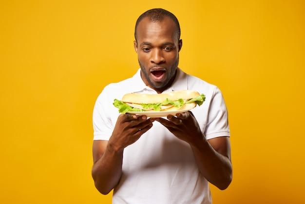 Excited black man holds big sandwich. Premium Photo