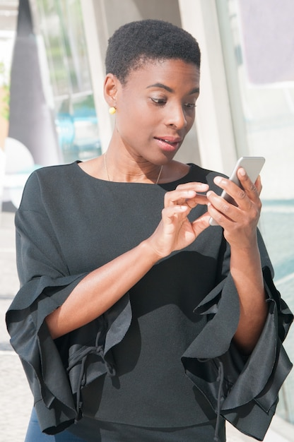 Excited black woman dialing number on mobile phone Free Photo