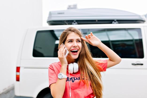 ピンクのシャツと白いヘッドフォンを身に着けている興奮したブロンドの女の子が友人と電話で話し、遠くを見ている 無料写真