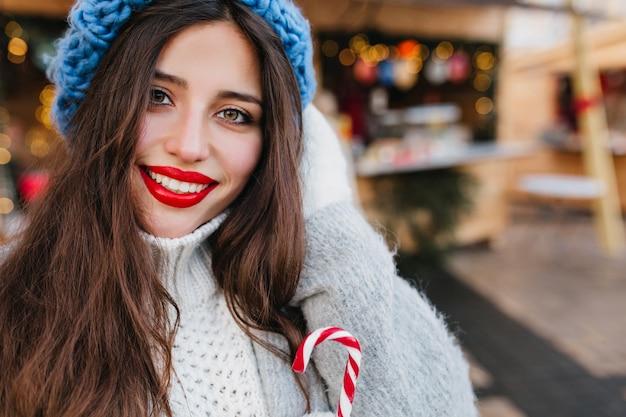 Возбужденная женщина брюнет с карими глазами пьет чай на улице нерезкости. фотография на открытом воздухе великолепной темноволосой дамы в пальто и синей шляпе, держащей чашку горячего кофе в холодный день. Бесплатные Фотографии
