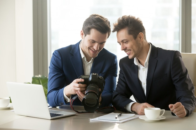 Excited businessman holding professional camera, showing photogr Free Photo