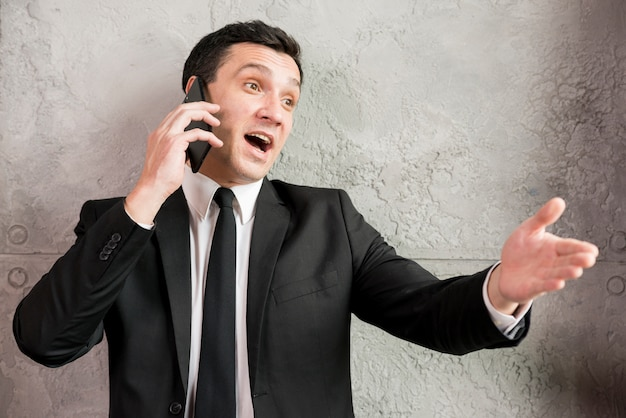 Excited businessman speaking on phone and pointing away Free Photo