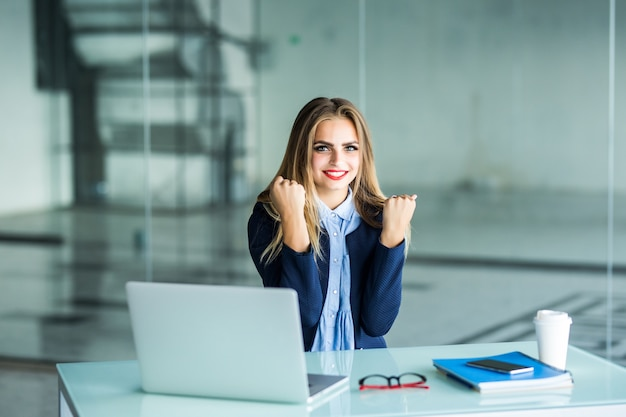 Excited businesswoman winning after achievement reading a smart phone sitting in a desktop at office Free Photo