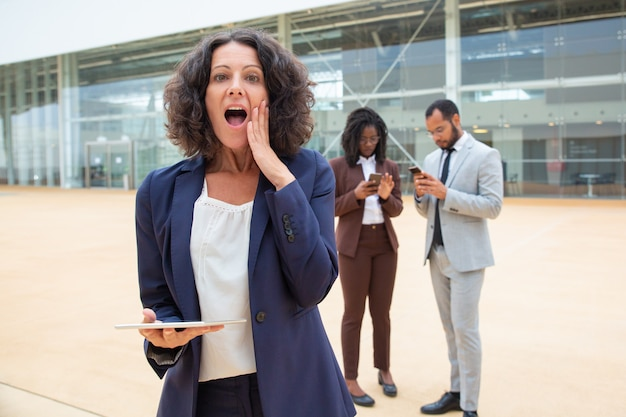 Excited businesswoman with tablet getting great shocking news Free Photo