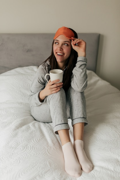 パジャマとスリーピングマスクで興奮した魅力的な女の子が目覚め、朝のコーヒーを飲みながら悪者に座っていた。自宅で幸せな日。 無料写真