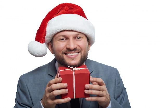 Uomo d'affari allegro eccitato alzando un piccolo regalo di natale in faccia sorridendo Foto Gratuite