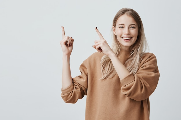 Excited cheerful european woman with long blonde hair, wearing casual clothes and smiling happily, pointing index fingers upwards Free Photo