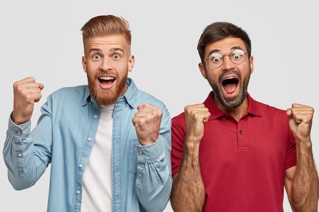Возбужденный веселый небритый парень празднует победу или триумф, сжимает кулаки, смотрит Бесплатные Фотографии
