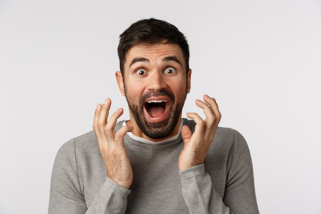 Excited, cheerful and upbeat good-looking bearded man in grey sweater, hear amazing news, shaking hands near face and shouting astonished, winning, receive prize, achieve goal Premium Photo