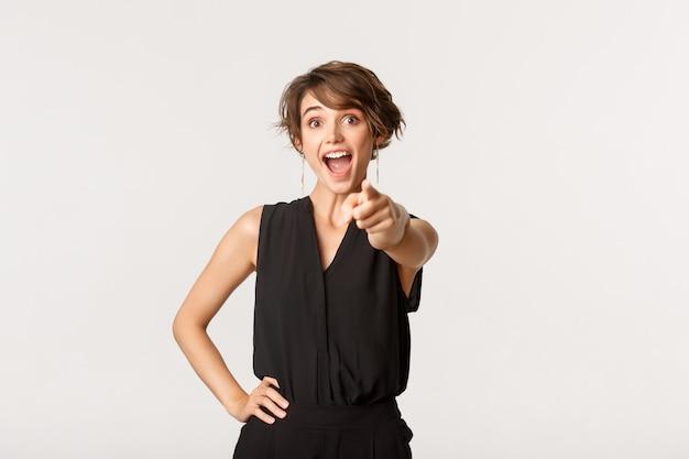 Возбужденная веселая молодая женщина, указывая пальцем на камеру с радостью, выбирая вас. Premium Фотографии