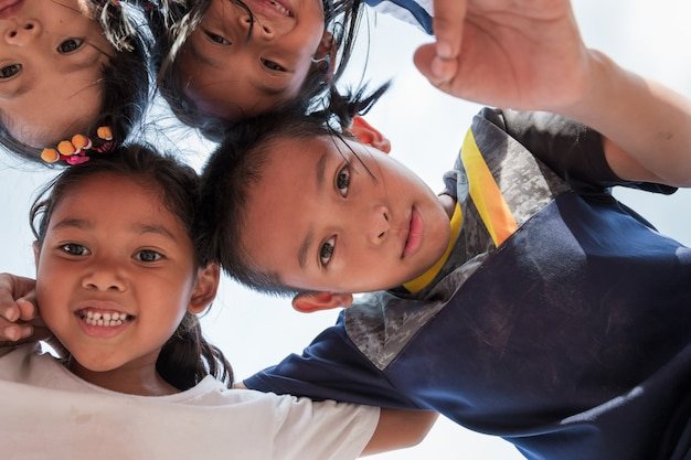 Excited children stand in circle hugging looking at camera at playing together Premium Photo