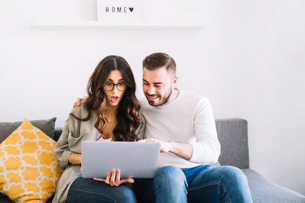 Excited couple using laptop Free Photo