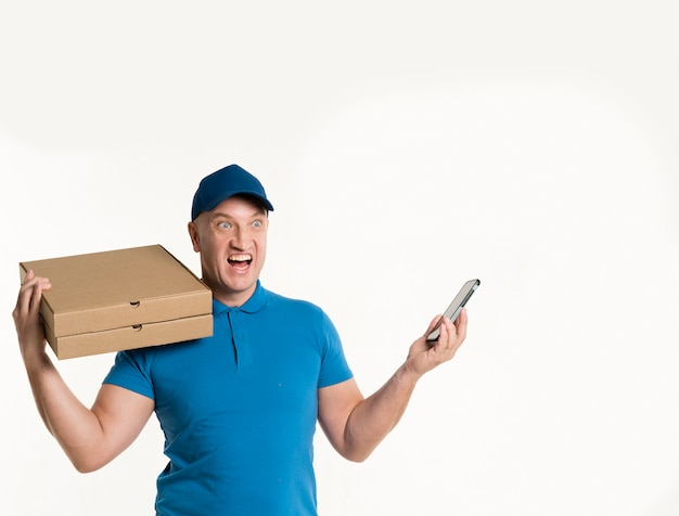 Excited delivery man holding phone and pizza boxes Free Photo