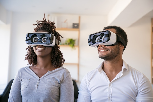 Excited diverse colleagues testing vr headset Free Photo