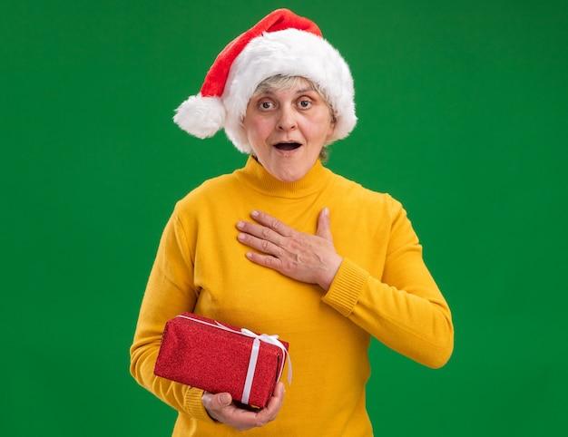 산타 모자와 함께 흥분된 노인 여성 가슴에 손을 넣고 복사 공간이 보라색 배경에 고립 된 크리스마스 선물 상자를 보유 무료 사진