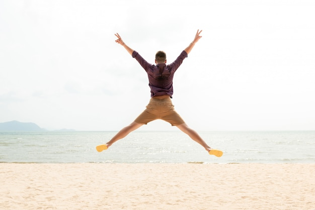 Excited energetic happy man jumping at the beach Premium Photo