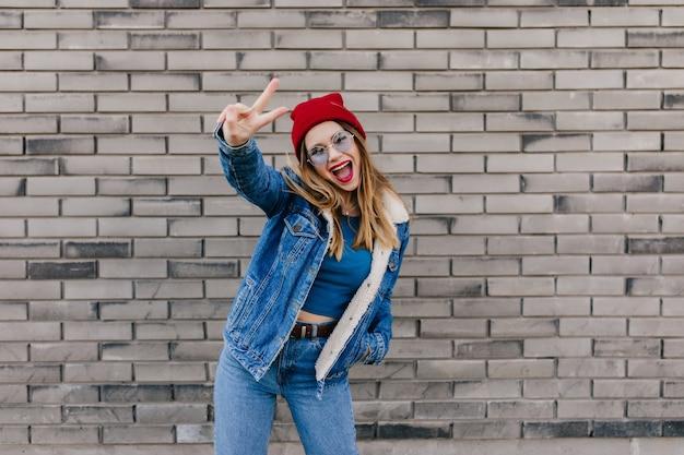 Возбужденная европейская женщина с счастливыми танцами выражения лица на кирпичной стене. открытый выстрел позитивной стильной девушки в красной шляпе, дурачящейся на улице. Бесплатные Фотографии