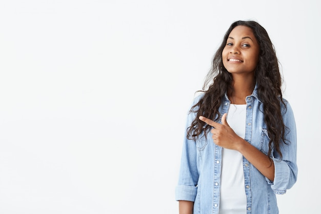 Excited and fascinated young dark-skinned female student in light-blue shirt and long wavy hair indicating something great on white wall with copy space for your text or promotional content. Free Photo