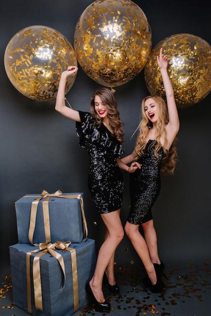金色のティンセルが付いた大きな風船で新年のパーティーを祝う豪華な黒のドレスを着た興奮したファッショナブルな若い女性。楽しんで、プレゼントして、積極性を表現してください。 無料写真