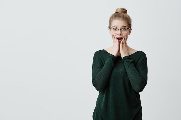 Взволнованная девушка-блондинка с узлом для волос и стильными очками смотрит с невероятным взглядом, удивленным, чтобы получить неожиданный подарок от родственников. люди, мимика, концепция эмоций Бесплатные Фотографии