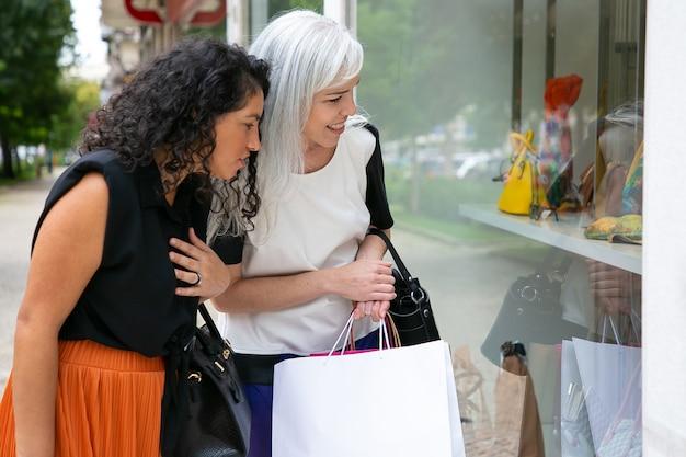 쇼핑 가방을 들고 외부 상점에 서서 상점 창에서 액세서리를 쳐다보고 흥분된 여자 친구. 측면보기. 윈도우 쇼핑 개념 무료 사진