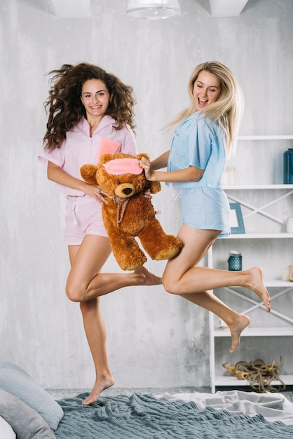 Excited female friends with jumping over bed with soft toy Free Photo
