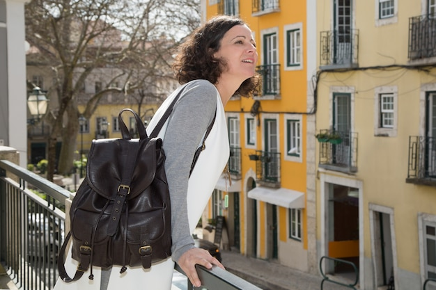 Excited female tourist admiring view from balcony Free Photo
