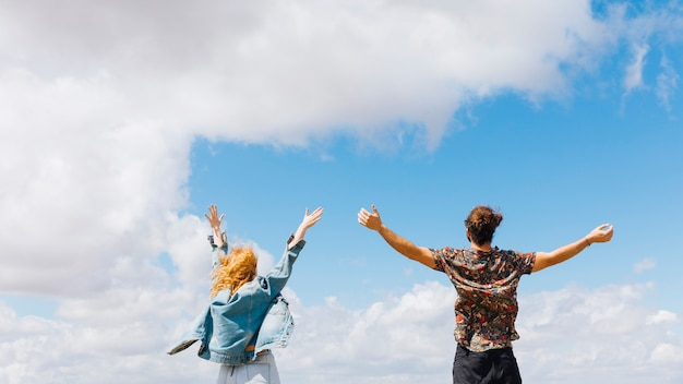 Excited and free couple with hands up Free Photo