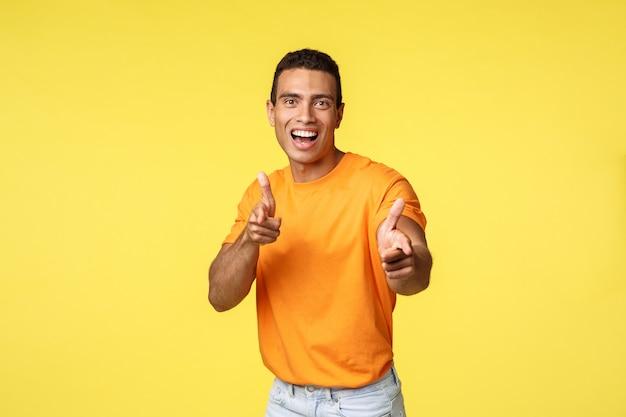 オレンジ色のtシャツで興奮してフレンドリーで発信若いハンサムな男 Premium写真