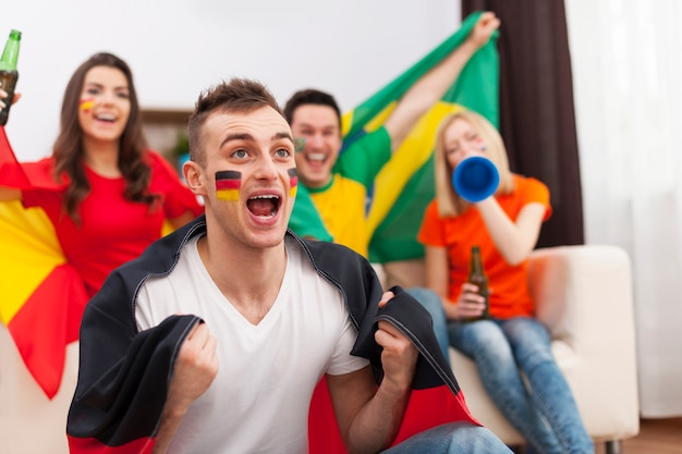 Excited german man with her friends cheering football match Free Photo