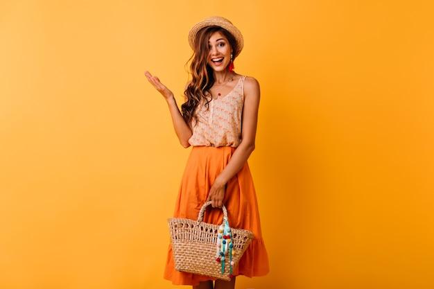 わらのバッグを保持している帽子の興奮した生姜の女性。良い一日を楽しんでいる夏服の恍惚とした長髪の女の子。 無料写真