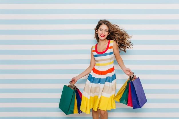 Возбужденная девушка смешно танцует на синей полосатой стене. внутреннее фото веселой дамы, наслаждающейся продажами во время покупок. Бесплатные Фотографии