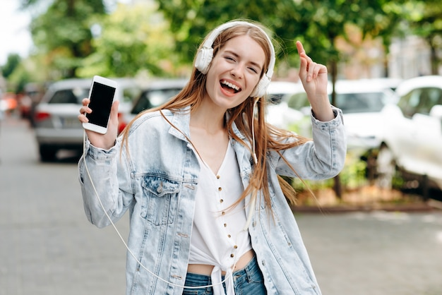 Excited girl  listen to music in an earphones and dancing outdoor showing a smartphone Premium Photo